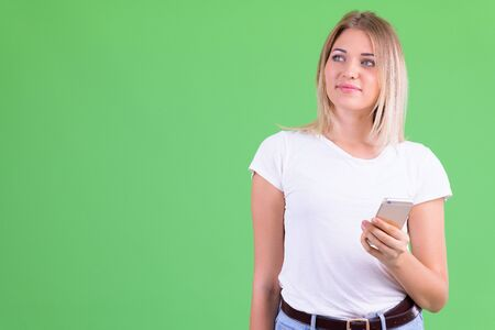 Young beautiful blonde woman thinking while using phone