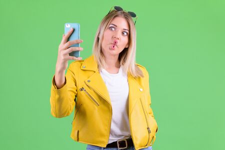 Young rebellious blonde woman making funny face and taking selfie