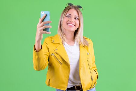 Happy young rebellious blonde woman taking selfie