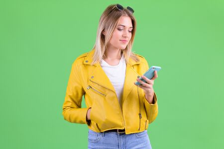 Portrait of young rebellious blonde woman using phone