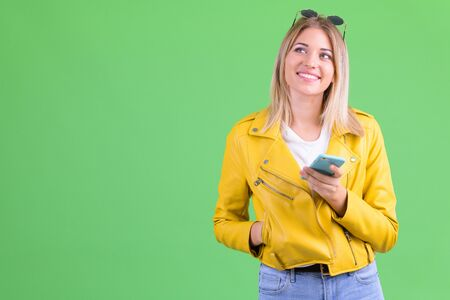 Happy young rebellious blonde woman thinking while using phone