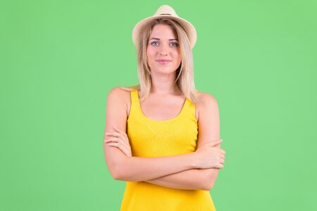 Young beautiful blonde tourist woman with arms crossed