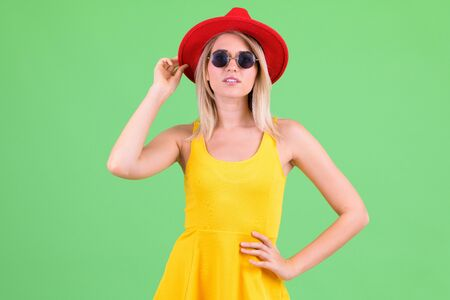 Young beautiful blonde tourist woman wearing red hat and sunglasses