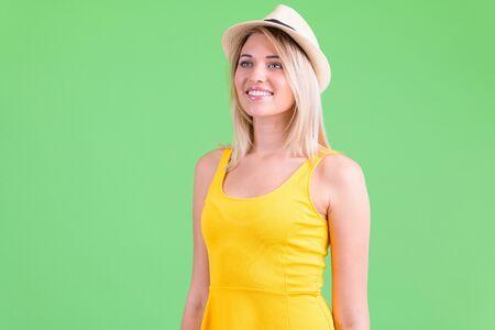 Happy young beautiful blonde tourist woman thinking