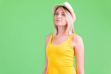Portrait of young beautiful blonde tourist woman thinking