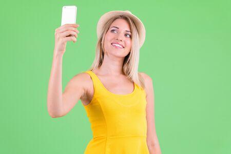 Happy young beautiful blonde tourist woman taking selfie