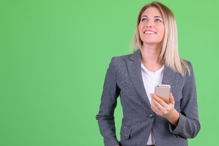 Happy young beautiful blonde businesswoman thinking while using phone Foto de archivo - 129176891