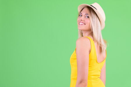 Profile view of happy young beautiful blonde tourist woman looking at camera Foto de archivo - 129176899