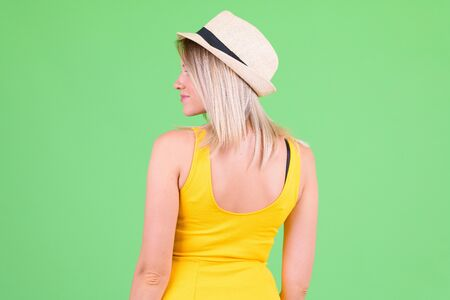 Rear view of young beautiful blonde tourist woman looking over shoulder
