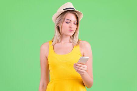 Young beautiful blonde tourist woman using phone