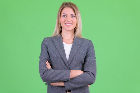 Happy young beautiful blonde businesswoman smiling with arms crossed Foto de archivo - 129176903