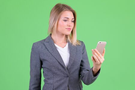 Portrait of young beautiful blonde businesswoman using phone