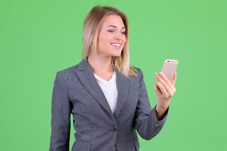 Happy young beautiful blonde businesswoman using phone