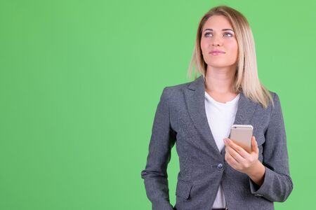 Young beautiful blonde businesswoman thinking while using phone