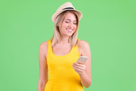 Happy young beautiful blonde tourist woman using phone