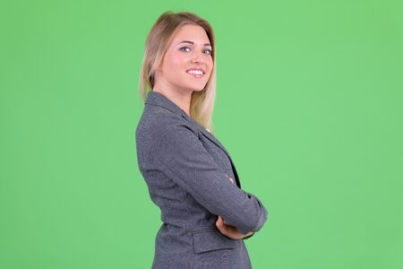 Profile view of happy young beautiful blonde businesswoman looking at camera Foto de archivo - 129176916
