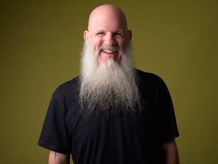Happy mature bald man with long gray beard smiling and laughing Foto de archivo - 129176964
