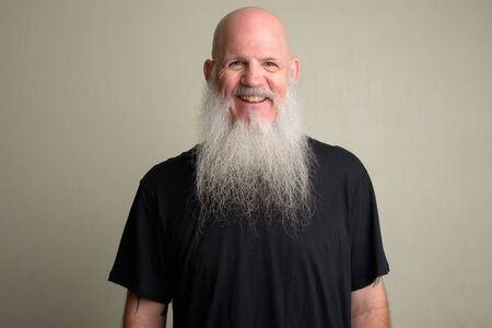 Happy mature bald man with long gray beard smiling and laughing Foto de archivo - 129176992