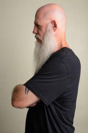 Profile view of mature bald man with long gray beard