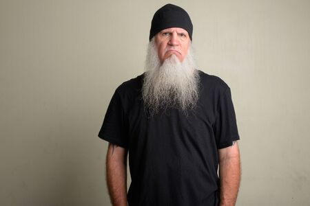 Angry mature man with long gray beard wearing beanie hat