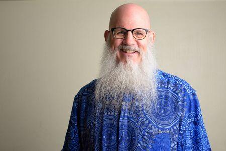 Happy mature bald man with long gray beard smiling and wearing eyeglasses Foto de archivo - 129177079