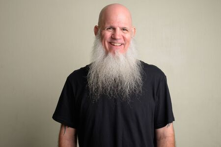Happy mature bald man with long gray beard smiling and laughing Foto de archivo - 129177093