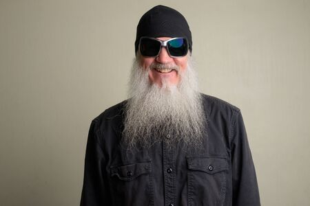 Happy mature man with long gray beard wearing beanie hat and sunglasses