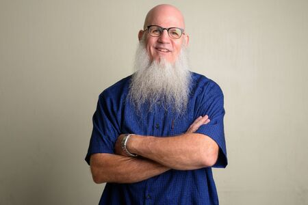 Happy mature bearded bald man smiling and wearing eyeglasses with arms crossed Foto de archivo - 129177150