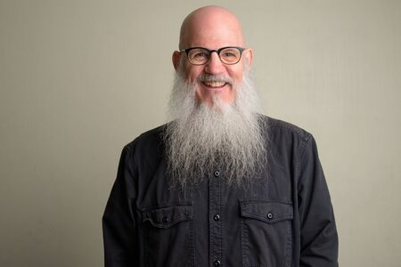 Happy mature bald man with long gray beard smiling and wearing eyeglasses Foto de archivo - 129177160