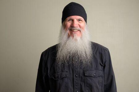 Happy mature man with long gray beard wearing beanie hat Foto de archivo - 129177165