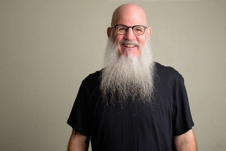 Happy mature bald man with long gray beard smiling and wearing eyeglasses Foto de archivo - 129177168