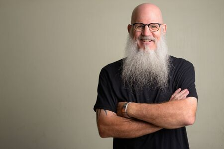 Happy mature bearded bald man wearing eyeglasses with arms crossed Foto de archivo - 129177202