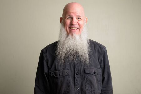 Happy mature bald man with long gray beard smiling and laughing Foto de archivo - 129177225