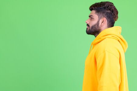 Profile view of young overweight bearded Indian man Фото со стока