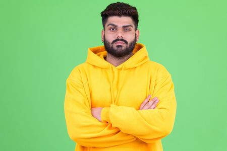 Young overweight bearded Indian man with arms crossed