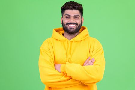 Happy young overweight bearded Indian man smiling with arms crossed