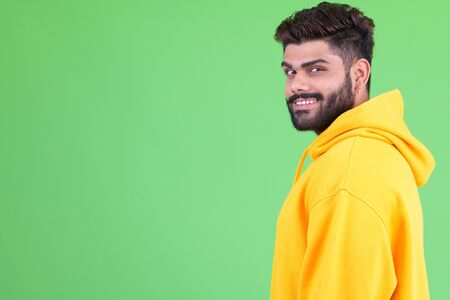 Profile view of happy young overweight bearded Indian man looking at camera