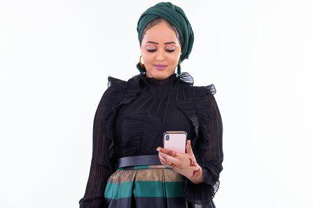 Junge schöne afrikanische muslimische Frau mit Telefon