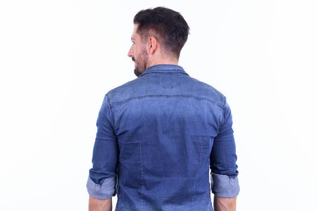 Rear view of young bearded hipster man looking over shoulder