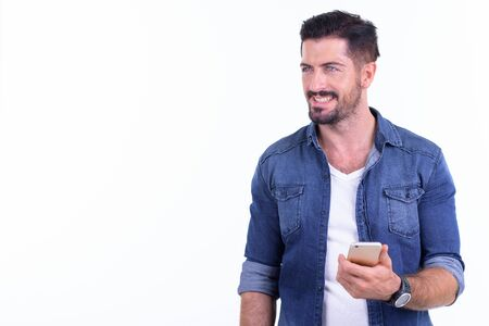 Happy young bearded hipster man thinking while using phone
