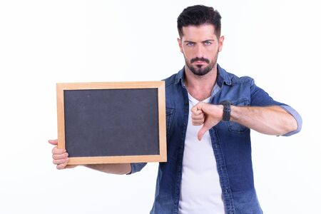 Stressed young bearded hipster man showing blackboard and giving thumbs down 写真素材 - 129634810