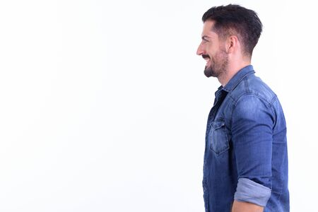 Profile view of happy young bearded hipster man smiling