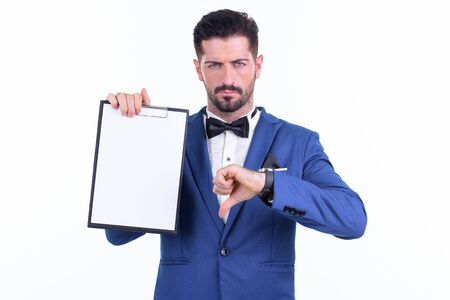 Stressed young bearded businessman showing clipboard and giving thumbs down