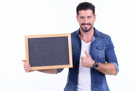 Happy young bearded hipster man showing blackboard and giving thumbs up