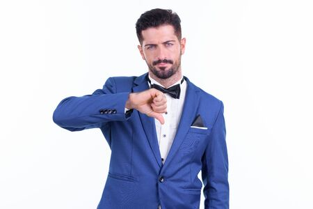 Stressed young bearded businessman giving thumbs down 写真素材 - 129635043