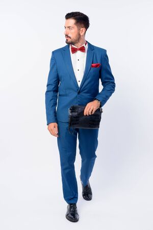 Full body shot of young handsome bearded businessman in blue suit Imagens