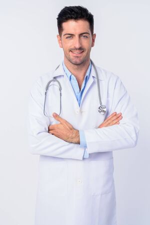 Portrait of happy young handsome man doctor smiling with arms crossed Standard-Bild