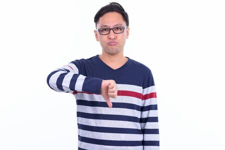 Stressed Japanese hipster man with eyeglasses giving thumbs down 写真素材