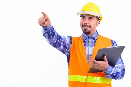 Happy bearded Persian man construction worker directing while holding clipboard