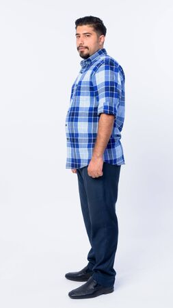 Full body shot profile view of bearded Persian hipster man looking at camera Stock Photo